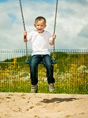 stock photo of swingset  - Little blonde boy having fun at the playground - JPG