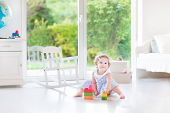 Adorable Toddler Girl With Curly Hair Wearing A Blue Dress Playing In A White Sunny Bedroom With A B