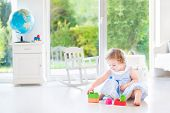 Cute toddler girl with curly hair wearing a blue dress playing in a white sunny bedroom
