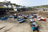 Coverack Cornwall with boats in the harbour at low tide in the late summer sunshine