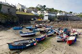 Boats in the harbour at low tide Coverack Cornwall in the late summer sunshine