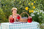 elderly woman with  jar of plum compote