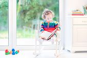 Cute Little Toddler Girl Reading A Book In A White Rocking Chair At A Big Window To The Garden