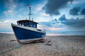 Blue Bboat On A Shingle Beach