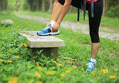 woman hiker tying shoelace in grenn grass