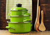 set of metal green pots cookware on a wooden background