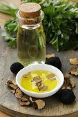 foto of truffle  - Olive oil flavored with black truffle on a wooden table - JPG