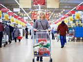 stock photo of grocery cart  - Women shopping in the supermarket with cart - JPG