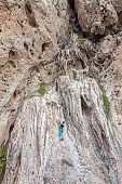 stock photo of incredible  - Woman climbing incredible wall Railay Beach in Thailand - JPG