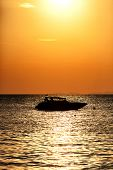 Silhouette Of A Motor Speed Boat At Sunset.