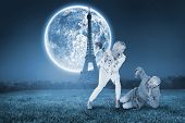 Angry woman attacking partner with rose bouquet against large moon over paris