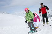 Family skiing down ski slope in winter