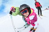 stock photo of family ski vacation  - Young girl learning how to ski with family - JPG