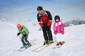 Ski teacher helping young kids to go down ski slope