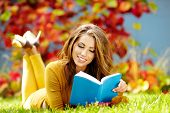 Portrait Of A Gorgeous Brunette Woman Reading A Book In The Autumn  Park.