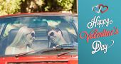 Loving couple in their red cabriolet having a ride against cute valentines message