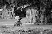 TORIT, SOUTH SUDAN-FEBRUARY 21, 2013: Unidentified woman cleans the area around her home in South Sudan