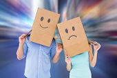 Couple wearing sad face boxes on their heads against blurry new york street