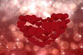 Love hearts against shimmering light design on red