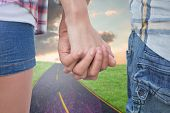 Couple in check shirts and denim holding hands against road on grass