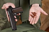Soldier Demonstrates Pistol And Cartridges To It