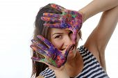 Woman Looks Out Her Hands Painted In Colorful Paint And Smiling