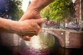 Elderly couple holding hands against canal in amsterdam