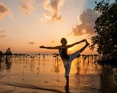 Woman practicing yoga on the beach near mangroves Woman practicing yoga on the beach near mangroves