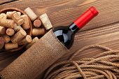 Red wine bottle and bowl with corks on wooden table background