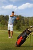 Young male golfer swinging golf club, following golf ball.