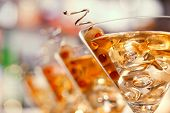 stock photo of shot glasses  - Several glasses of famous cocktail Martini shot at a bar with shallow depth of field - JPG