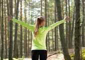 fitness, sport, happiness and people concept - happy woman raising hands over woods background from back