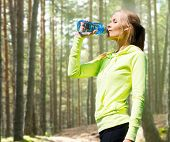 fitness, sport, people and thirst concept - happy woman drinking bottle water after doing sports over woods background