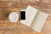 business, education, objects and technology concept - close up of notebook, coffee paper cup and smartphone on table