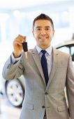 auto business, car sale, consumerism and people concept - happy man showing key at auto show or salon