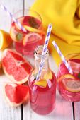 Pink lemonade in glasses and bottle on table close-up