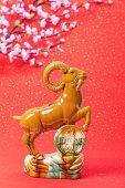 Ceramic goat souvenir on red paper