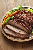stock photo of brisket  - barbecue beef brisket isolated on brown wooden board - JPG