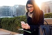 picture of woman  - Outdoor portrait of young beautiful woman using her mobile phone - JPG