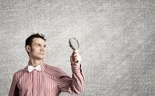 Young funny science man looking in magnifier