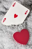 Red heart with ace of hearts in the snow