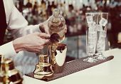 stock photo of toned  - Bartender is pouring liquor in golden shaker - JPG