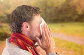 Man blowing nose on tissue against peaceful autumn scene in forest