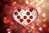 Heart shaped box of candy against light design shimmering on red