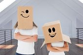 Mature couple wearing boxes over their heads against modern room