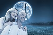 Smiling couple embracing and looking against large moon over paris