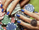 hands of young caucasian woman with red manicure at casino table