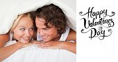 Couple under a duvet with a knowing smile against happy valentines day
