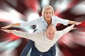 Happy mature couple having fun against digitally generated twinkling light design