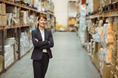 pic of warehouse  - Pretty warehouse manager smiling at camera in a large warehouse - JPG